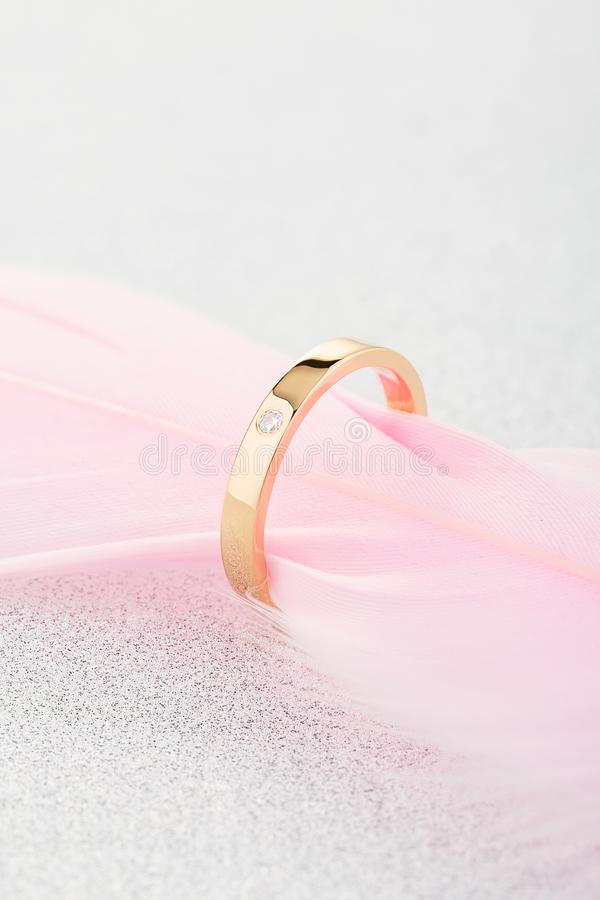 Anillo de oro del compromiso con un diamante en pluma rosada fotos de archivo
