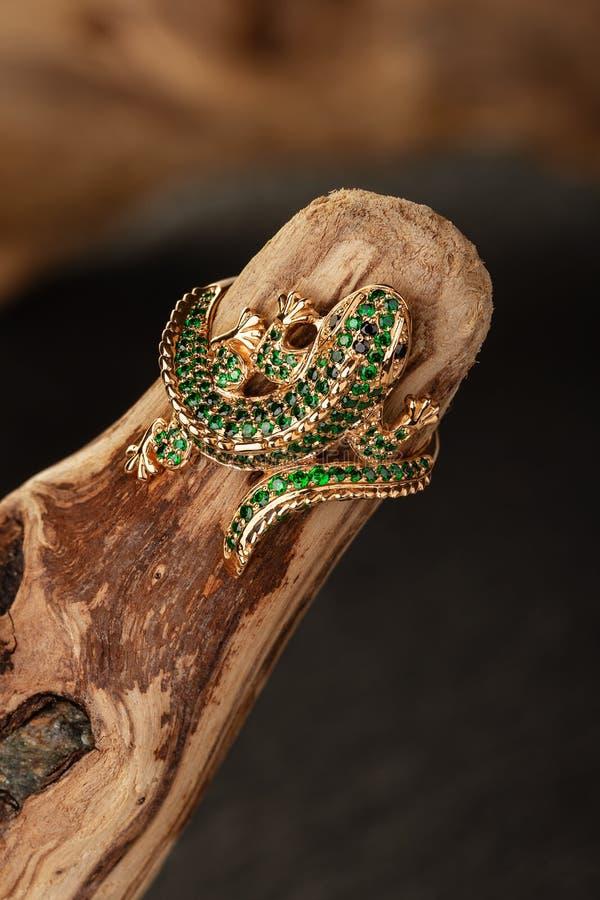 Anillo de oro de la joyería de la forma del lagarto con las piedras preciosas verdes en fondo de madera natural fotografía de archivo