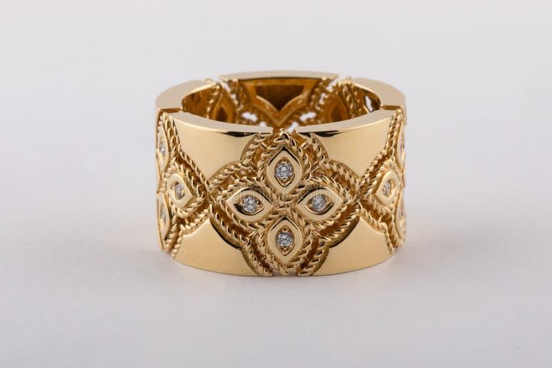 Anillo de oro para mujer con los diamantes, bajo la forma de flores aisladas en un fondo blanco imagen de archivo