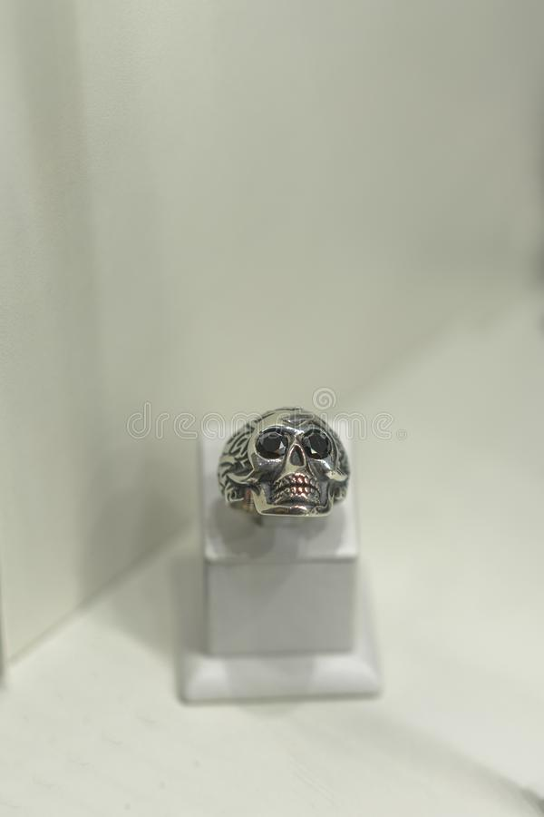 Anillo de plata bajo la forma de cráneo en una vela en una tienda foto ertical fotos de archivo