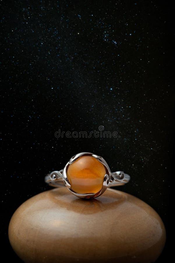 Anillo de plata con el cabochon de piedra ambarino con el cielo nocturno imágenes de archivo libres de regalías