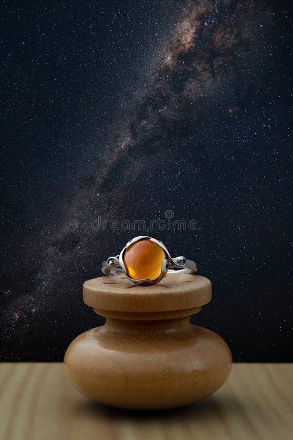 Anillo de plata con el cabochon de piedra ambarino con el cielo nocturno imagenes de archivo