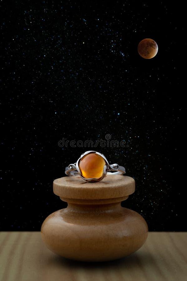Anillo de plata con el cabochon de piedra ambarino con el cielo nocturno fotografía de archivo