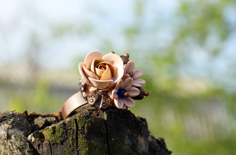 Anillo hecho a mano en una forma de flores de la arcilla del pol?mero imagenes de archivo