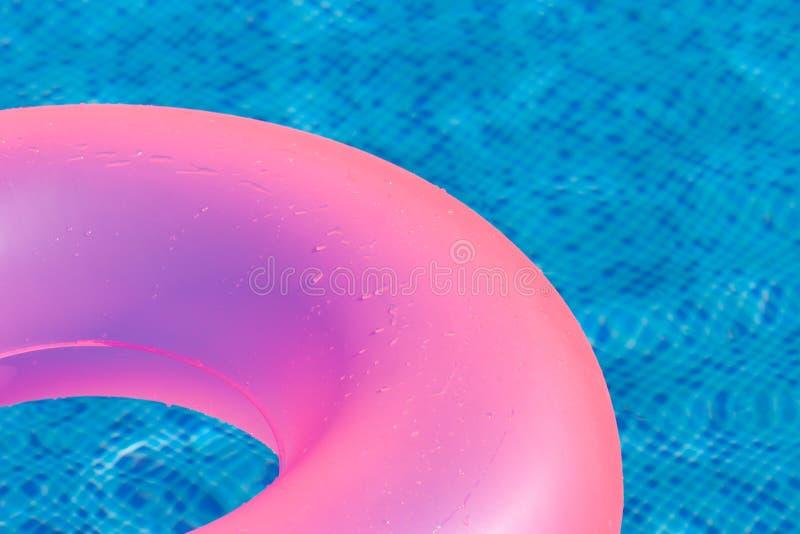 Anillo rosado flotante en swimpool del agua azul. fotos de archivo libres de regalías