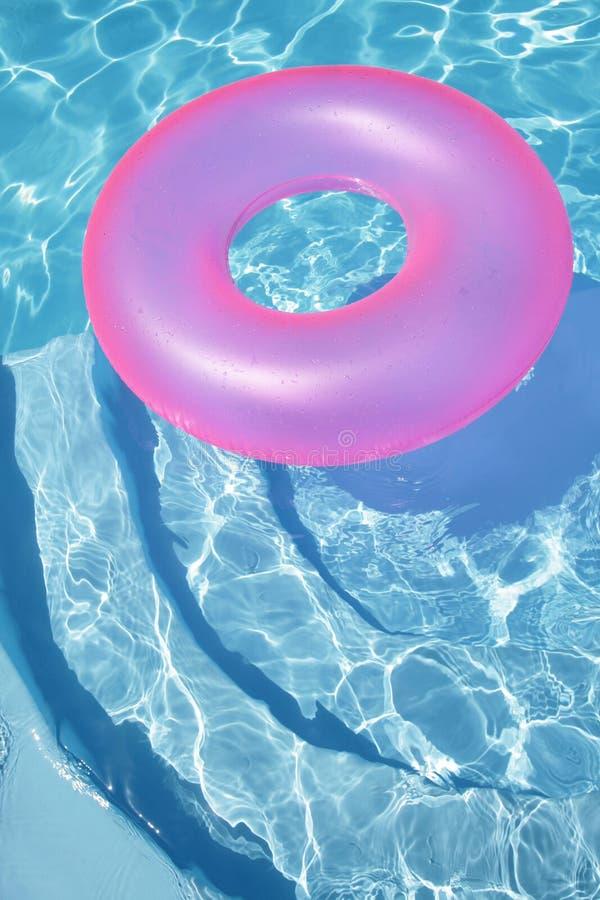 Anillo rosado que flota en una piscina azul foto de archivo libre de regalías