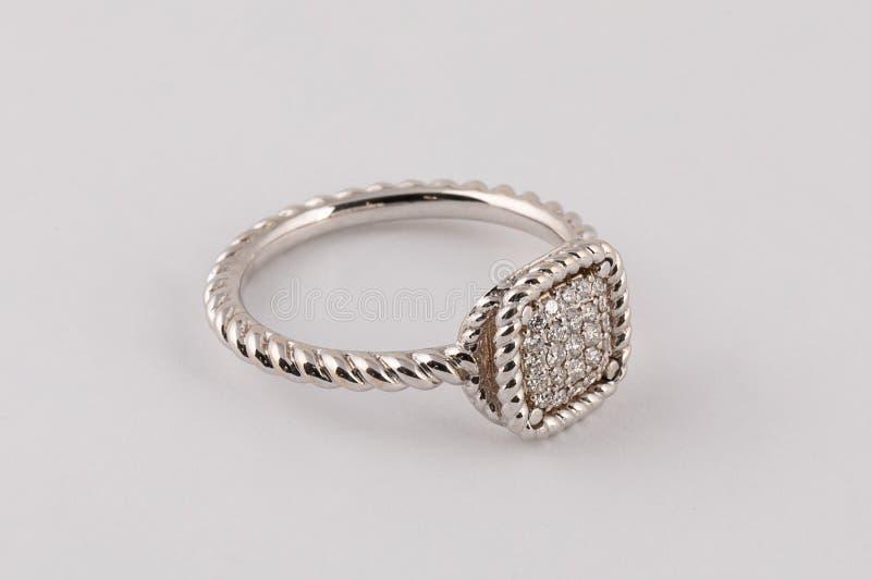 Anillo trenzado de plata para mujer con los diamantes en el centro con una franja aislada en un fondo blanco fotografía de archivo