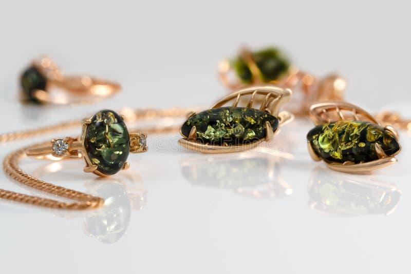 Anillo y pendientes de oro del primer con el ámbar verde báltico natural auténtico en superficie de acrílico imágenes de archivo libres de regalías