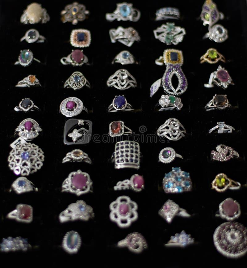 Anillos con las diversos piedras preciosas, materiales, tama?os y formas en la exhibici?n de una joyer?a foto de archivo libre de regalías