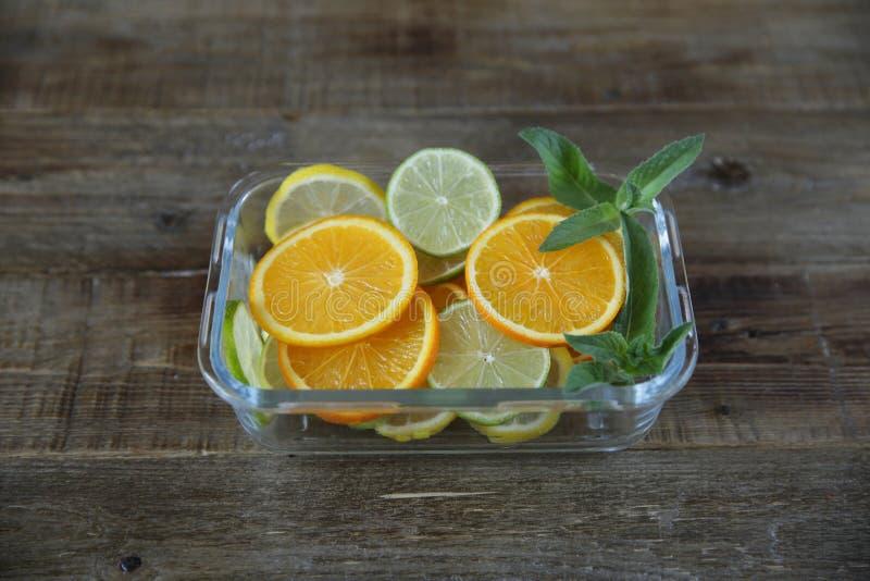 Anillos cortados de la naranja, del limón, de la cal y de la puntilla de la menta en una placa de cristal en un fondo rústico de  imagen de archivo