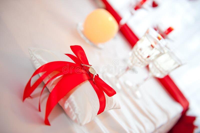 Anillos de bodas atados con una cinta roja con un corazón en un tiro del cojín contra la perspectiva de dos vidrios de champán fotografía de archivo libre de regalías