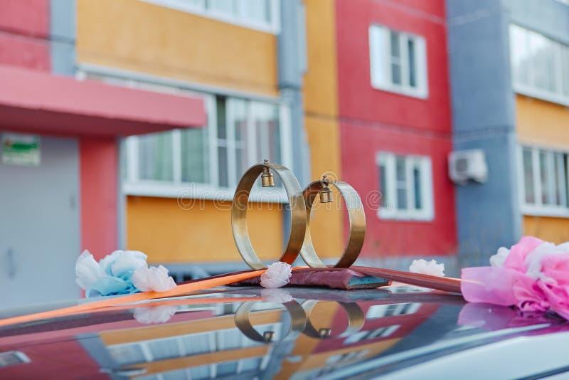 Anillos de bodas con las campanas en el tejado del coche, contra la perspectiva de edificios urbanos Decoración rusa tradicional  imagen de archivo libre de regalías