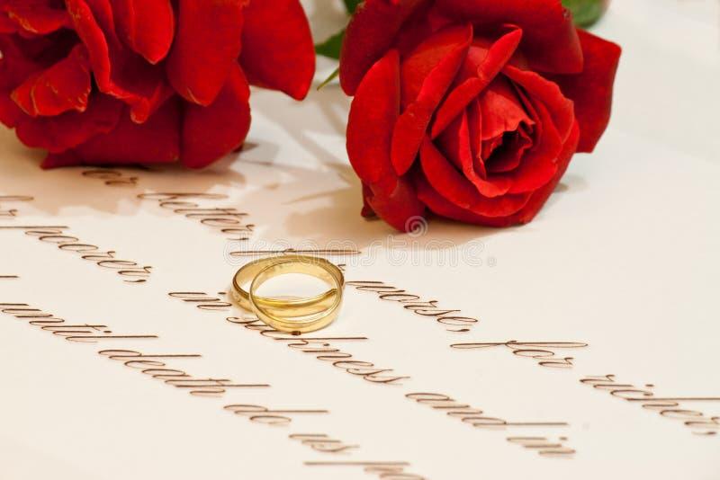 Anillos de bodas con las rosas y los votos fotos de archivo