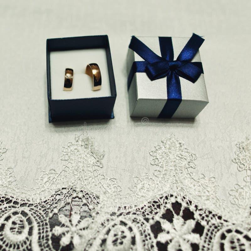 Anillos de bodas de oro costosos en una caja azul con un cierre de la cinta fotos de archivo