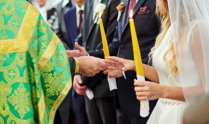Anillos de bodas del intercambio de los recienes casados en una ceremonia en la iglesia imagenes de archivo