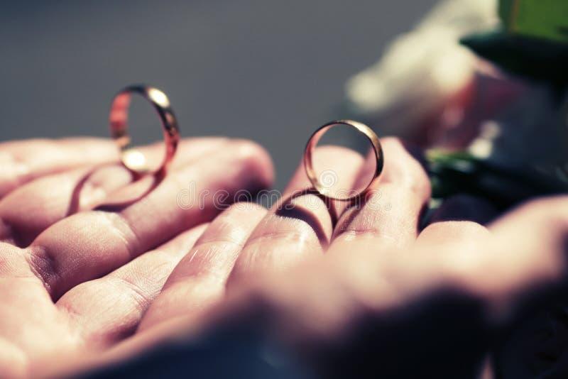 Anillos de bodas del oro en un ` s del hombre fotografía de archivo