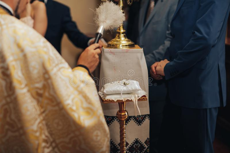 Anillos de bodas durante matrimonio santo en iglesia imagenes de archivo