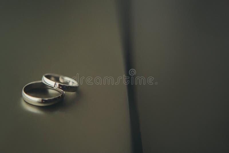 Anillos de bodas en el fondo oscuro fotografía de archivo