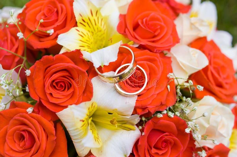 Anillos de bodas en el ramo imagenes de archivo