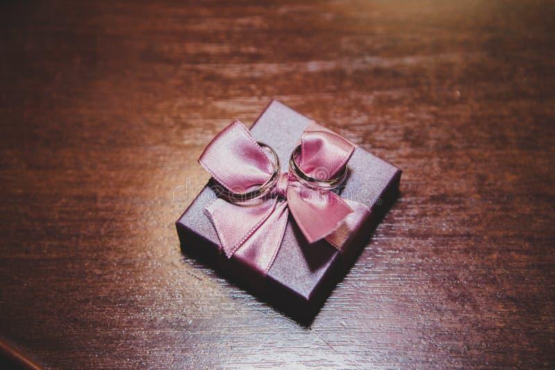 Anillos de bodas en el regalo con el arco foto de archivo