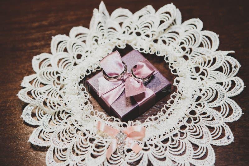 Anillos de bodas en el regalo con el arco foto de archivo libre de regalías