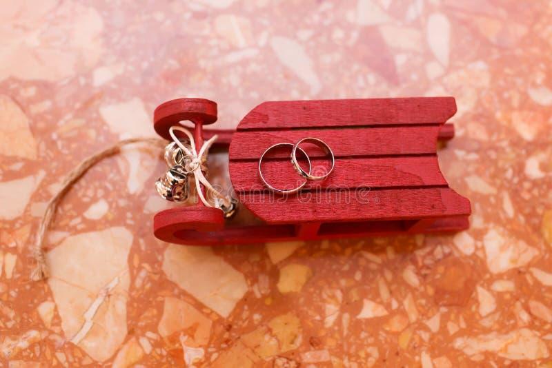 Anillos de bodas en el trineo rojo, fondo de la Navidad fotos de archivo libres de regalías