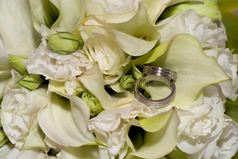 Anillos de bodas en flores imagen de archivo
