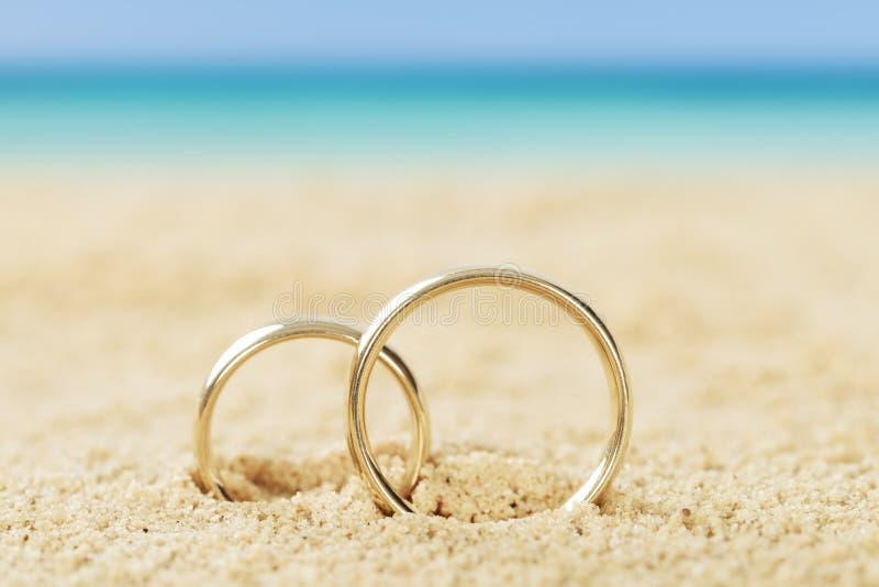 Anillos de bodas en la arena imagen de archivo libre de regalías