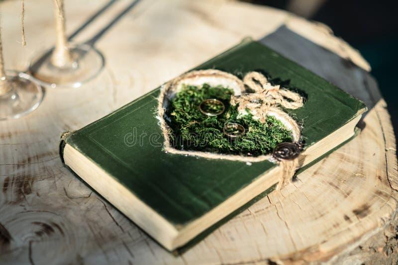Anillos de bodas en la hierba foto de archivo