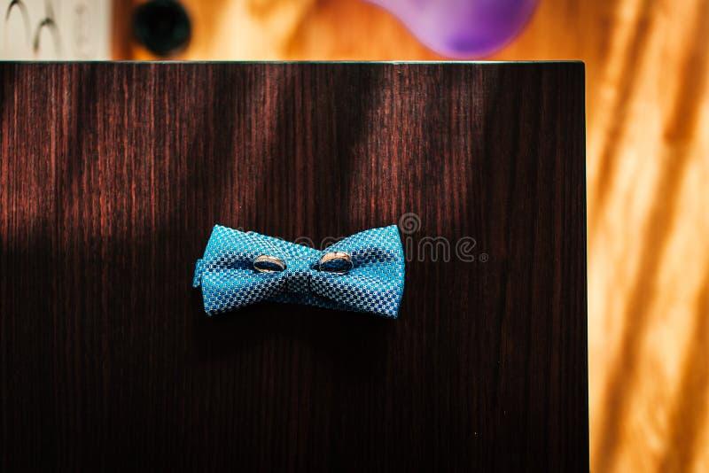 Anillos de bodas en la mariposa del novio en la tabla de madera foto de archivo libre de regalías