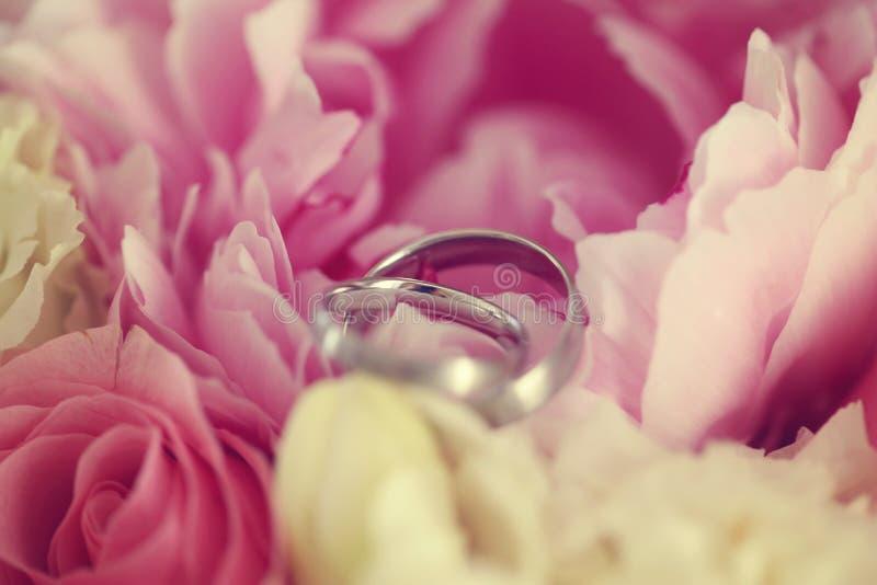 2 anillos de bodas en las flores imagenes de archivo