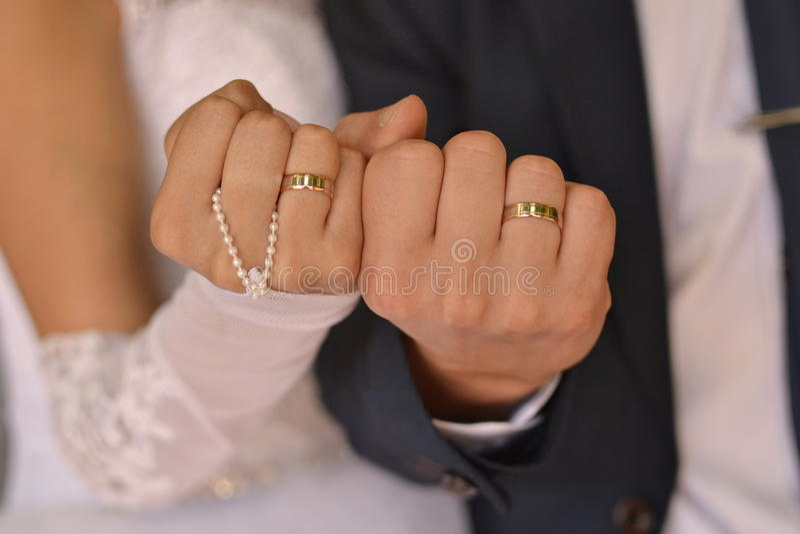Anillos de bodas en las manos foto de archivo