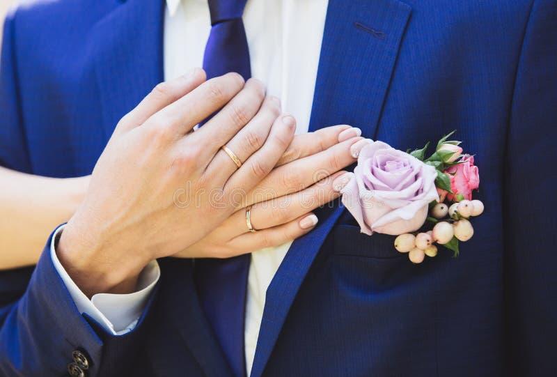 Anillos de bodas en las manos de la novia y del novio imagen de archivo