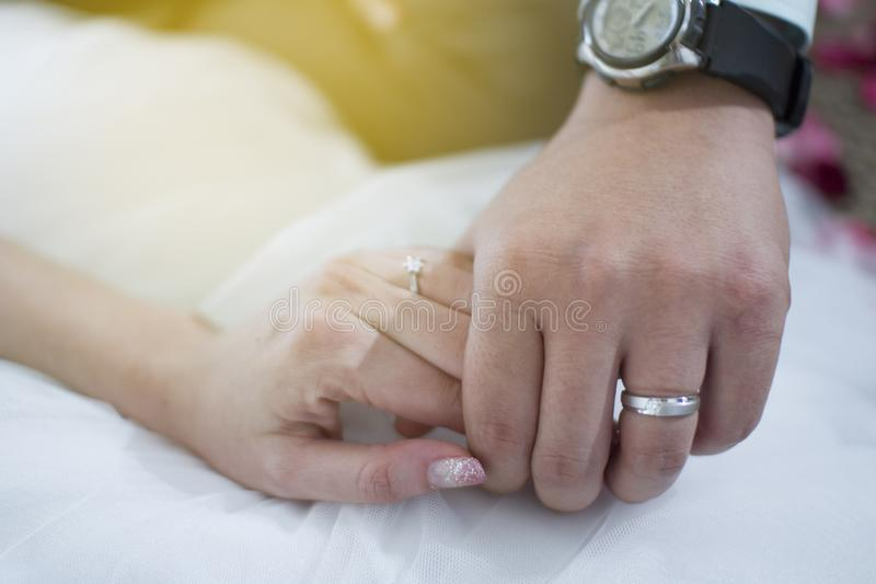 Anillos de bodas en las manos de novia y del novio pares dedicados que llevan a cabo las manos con el diamante y el anillo de pla imagen de archivo