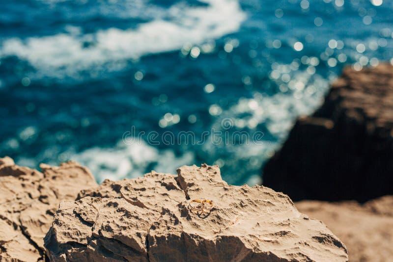 Anillos de bodas en las rocas cerca del mar fotos de archivo libres de regalías