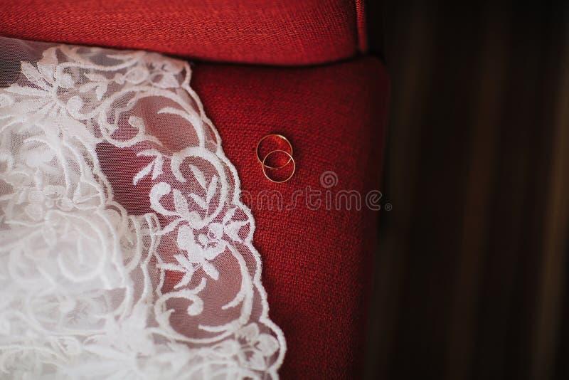 anillos de bodas en los vestidos del rojo de una boda del sofá fotos de archivo libres de regalías