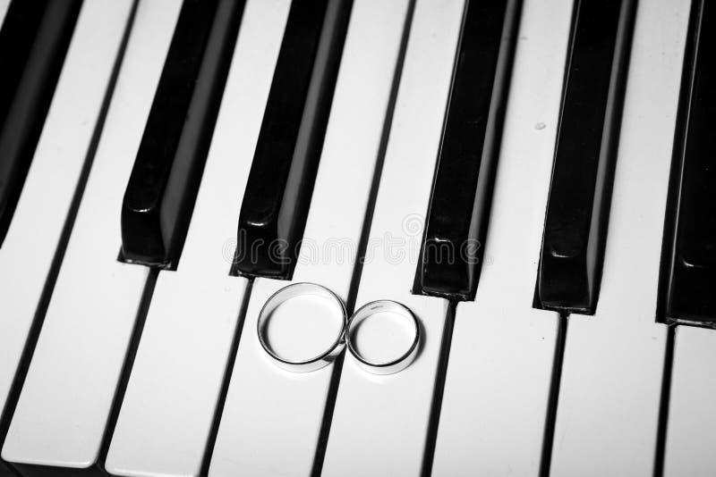 Anillos de bodas en piano foto de archivo