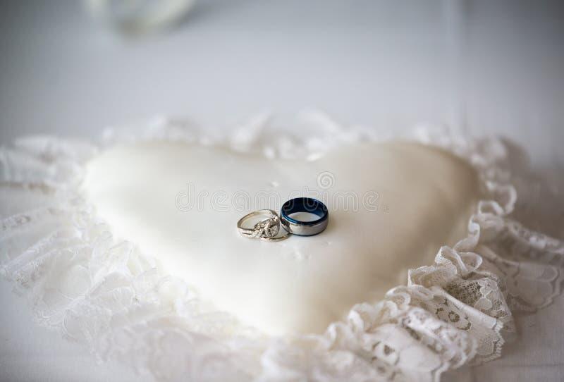 Anillos de bodas en una almohada en forma de corazón blanca fotos de archivo