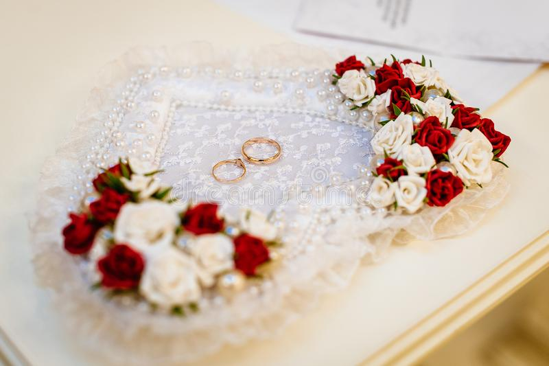 Anillos de bodas en una almohada en forma de corazón con las flores imagenes de archivo