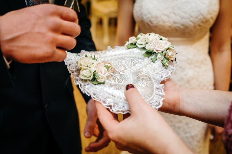 Anillos de bodas en una almohada en forma de corazón en el fondo de la novia y del novio imagen de archivo libre de regalías