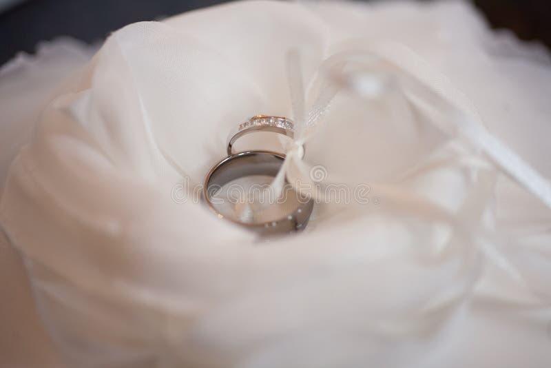 Anillos de bodas en una flor blanca y una almohada imagen de archivo