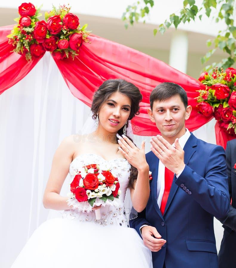 Anillos de bodas hermosos felices de la demostración de los recienes casados imágenes de archivo libres de regalías