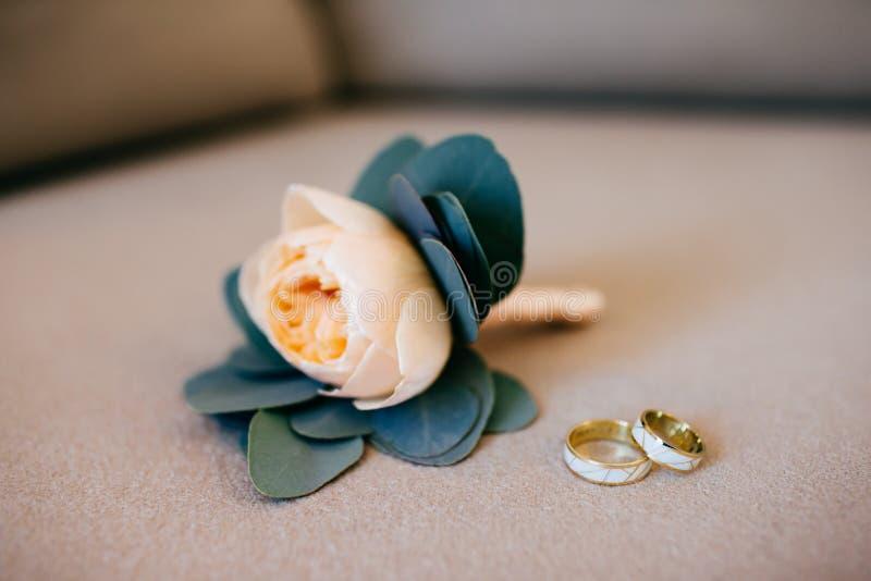 Anillos de bodas hermosos y bouquete nupcial que mienten en el fondo blanco Gran ramo nupcial de rosas y de anillos de oro El cas foto de archivo libre de regalías