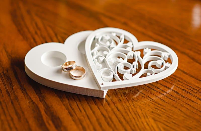 Anillos de bodas de los recienes casados en un soporte en forma de corazón de madera foto de archivo