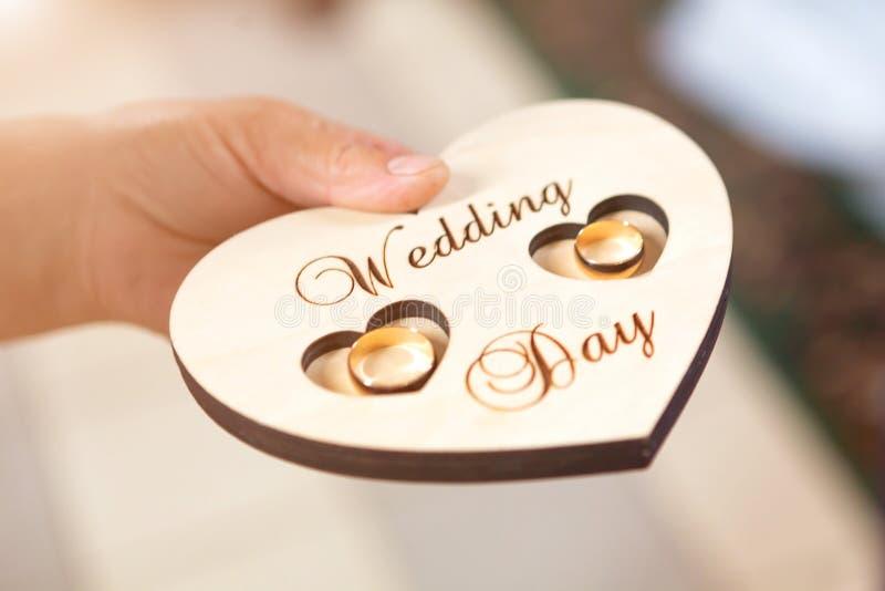 Anillos de bodas de los recienes casados en un soporte en forma de corazón de madera en la iglesia fotografía de archivo libre de regalías