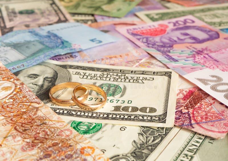 Anillos de bodas de oro en diverso fondo de los billetes de banco Boda de la conveniencia fotografía de archivo libre de regalías