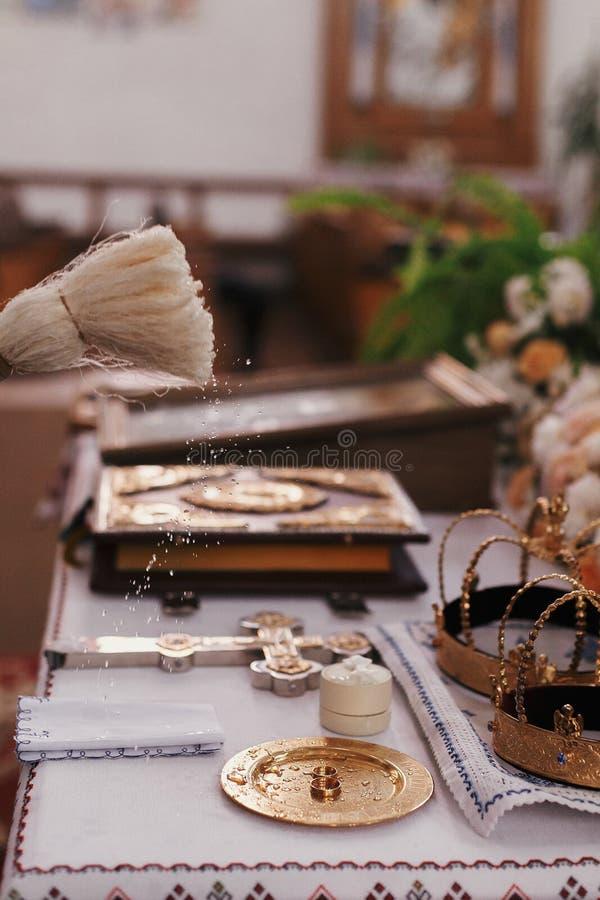 Anillos de bodas de oro de la bendición del sacerdote en el altar con agua santa W fotos de archivo