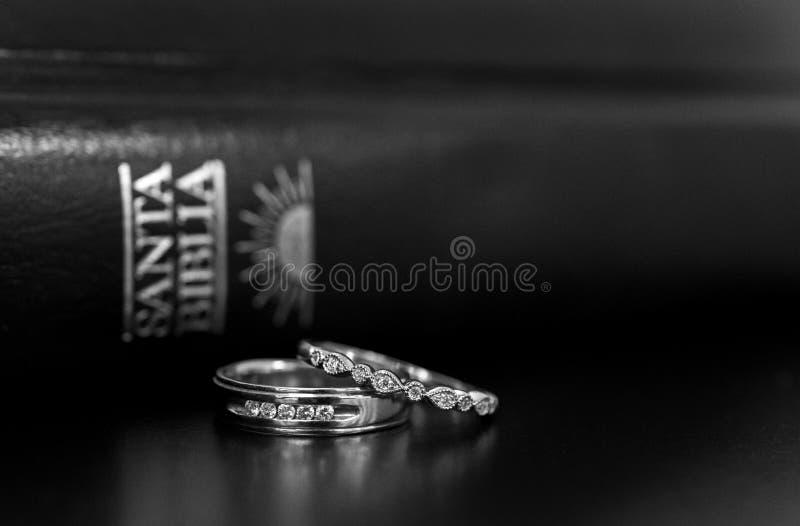 Anillos de bodas y biblia española fotos de archivo