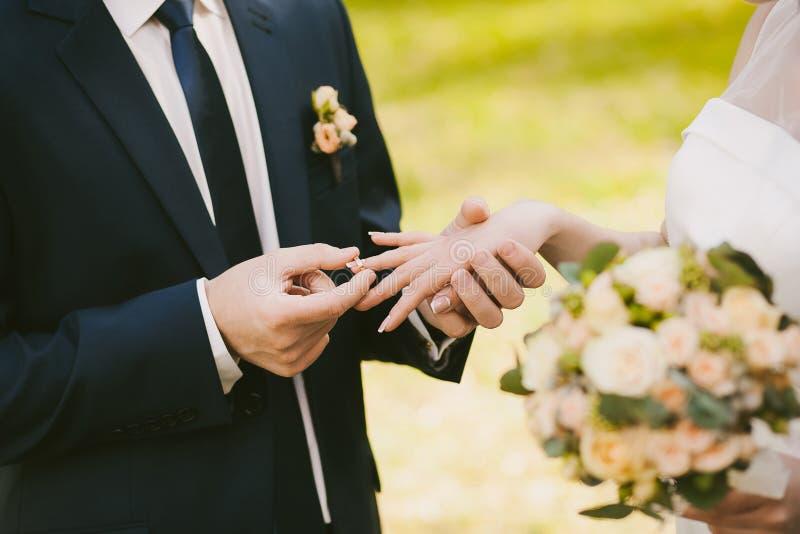 Anillos de bodas y manos de la novia y del novio fotos de archivo