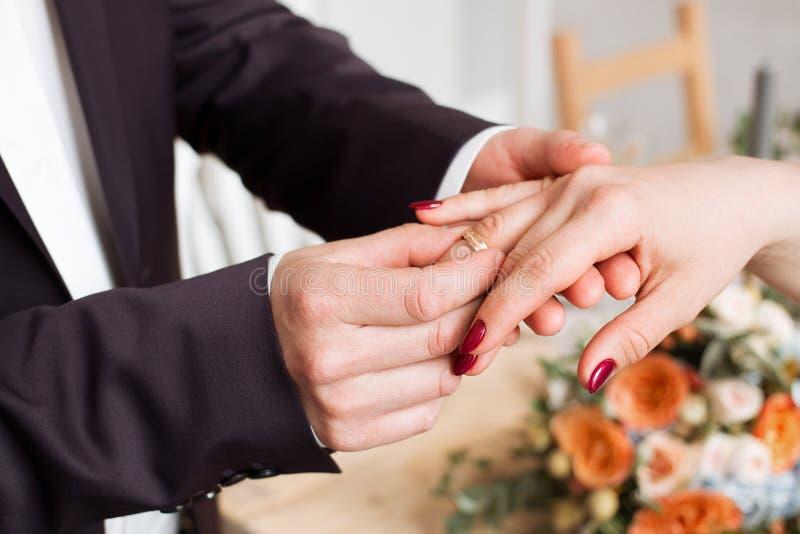 Anillos de bodas y manos de la novia y del novio pares jovenes de la boda en la ceremonia matrimonio Hombre y mujer en amor dos p fotos de archivo